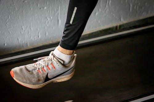 Person in Black Pants Wearing Nike Sneakers