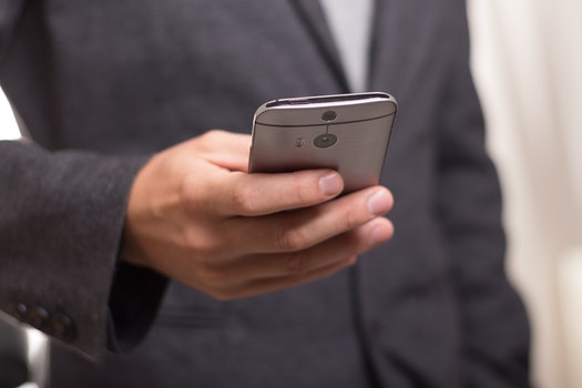 Man Wearing Black Suit Jacket Holding Gray Htc Android Smartphone