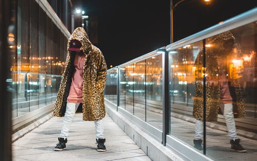 Man in Brown and Black Leopard Coat Walking on Sidewalk during Night Time