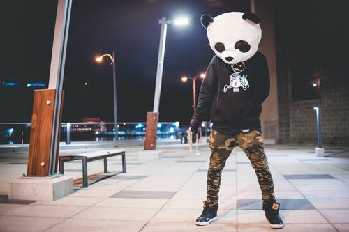 Person in Black and White Panda Head and Brown Pants Standing on Gray Concrete Floor