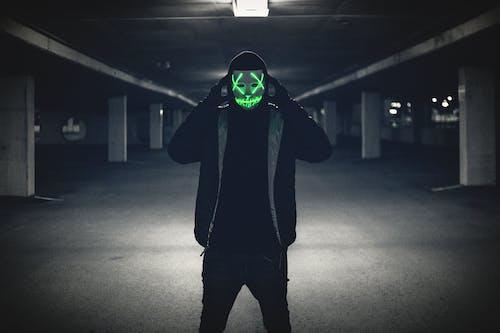 Man in Black Hoodie Wearing Green Mask