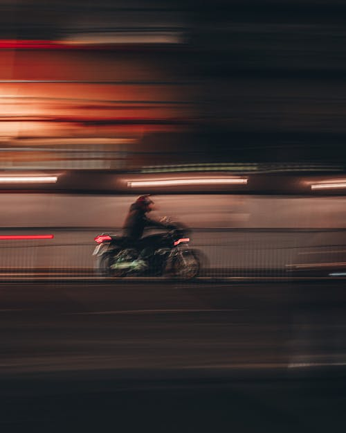 Man Riding Motorcycle on Road during Night Time
