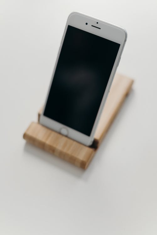 White Ipad on Brown Wooden Stand