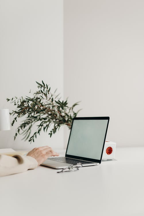 Person Using Black Laptop Computer on White Table