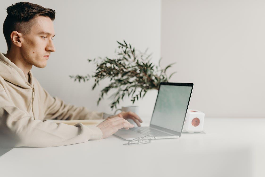 Woman in Gray Sweater Using Macbook Pro