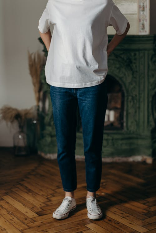 Photo of Person Wearing White T-Shirt and Blue Denim Jeans