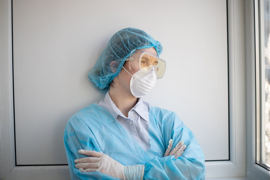 Woman in Blue Scrub Suit Wearing White Mask