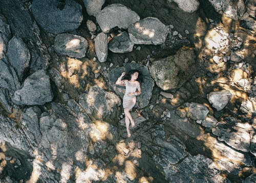 Photo Of Woman Laying On Top Of Rock