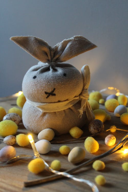 Easter decoration with handmade soft rabbit toy composed with small decorative eggs and garland lights against wall