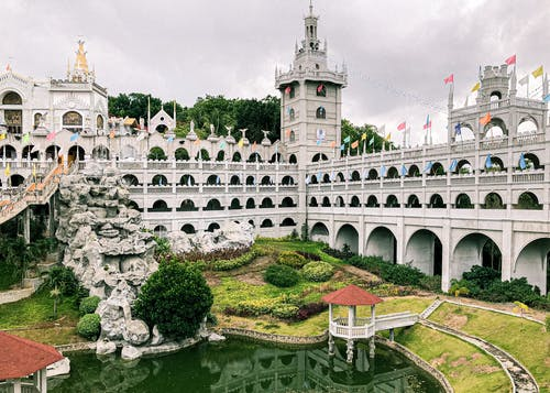 Ancient catholic Monastery of the Holy Eucharist with arched details located in well groomed park with pond in Cebu