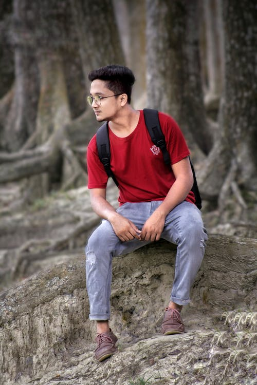 Man in Red Crew Neck T-shirt and Blue Denim Jeans Sitting on Gray Rock