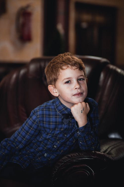 Boy in Blue Plaid Dress Shirt Sitting on Brown Leather Couch