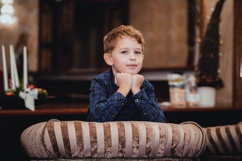 Boy Wearing Blue Plaid Shirt While Leaning on Sofa