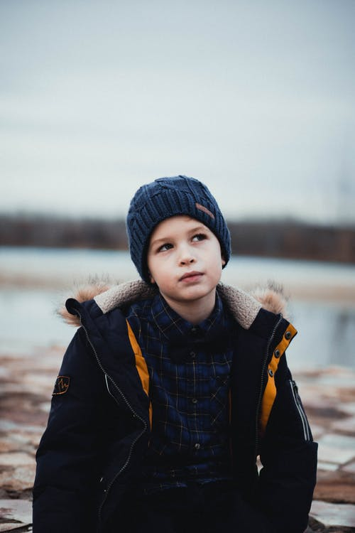 Photo of Boy Thinking While Wearing Black Jacket and Blue Beanie