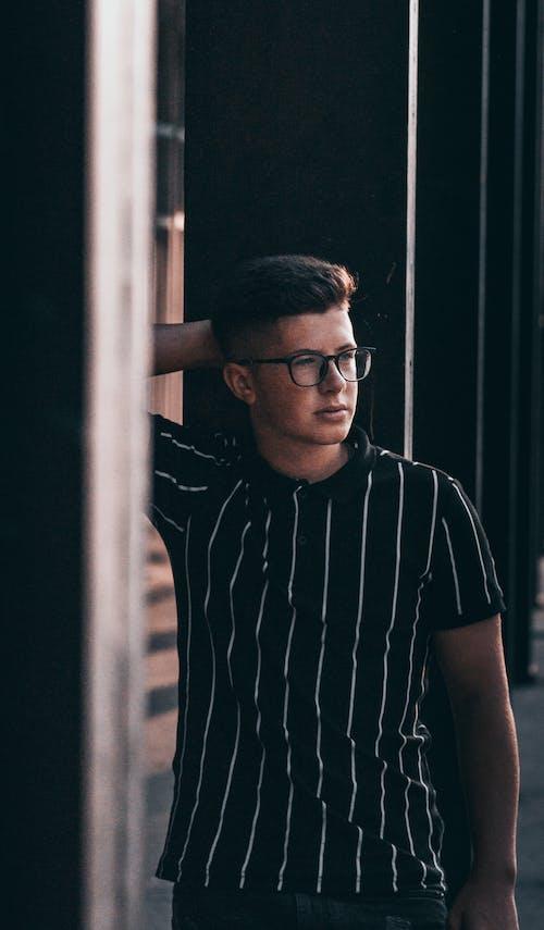 Man in Black and White Stripe Polo Shirt Wearing Black Framed Eyeglasses