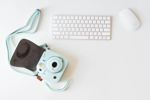 White Computer Keyboard Beside Blue Instax Camera