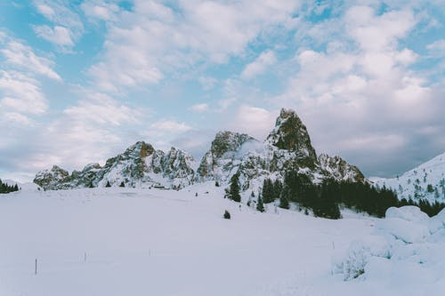 Photo Of Snow Covered Mountains Under Cloudy Sky