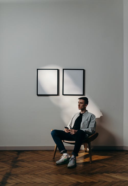Man in Gray Dress Shirt Sitting on Black Chair