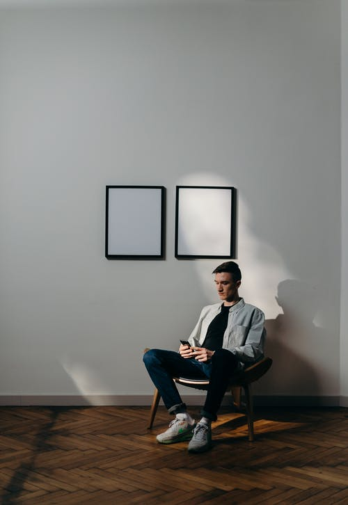 Man in White Dress Shirt Sitting on Black Chair