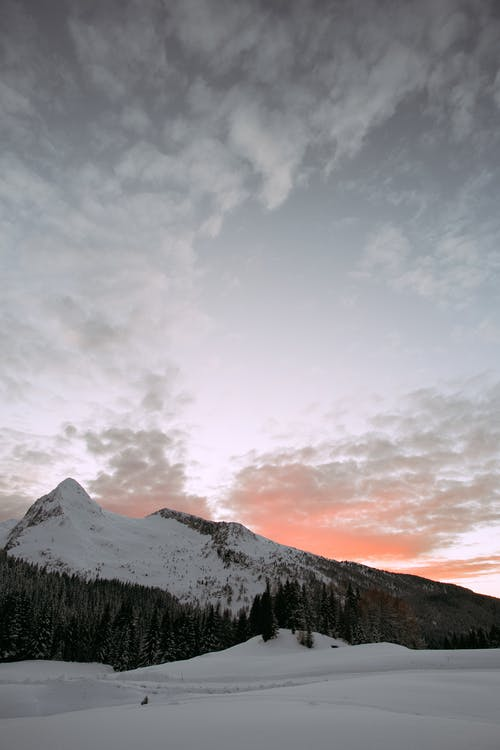 Photo Of Snow Covered Mountain Under Cloudy Sky
