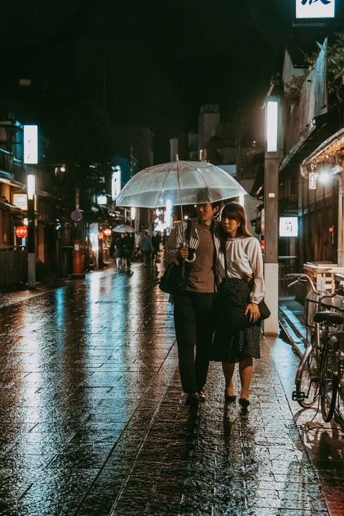 Couple Walking on Street Under Umbrella during Night Time