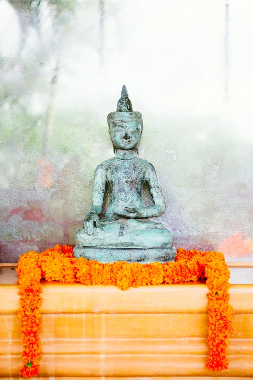 Gold Buddha Statue on Orange Textile