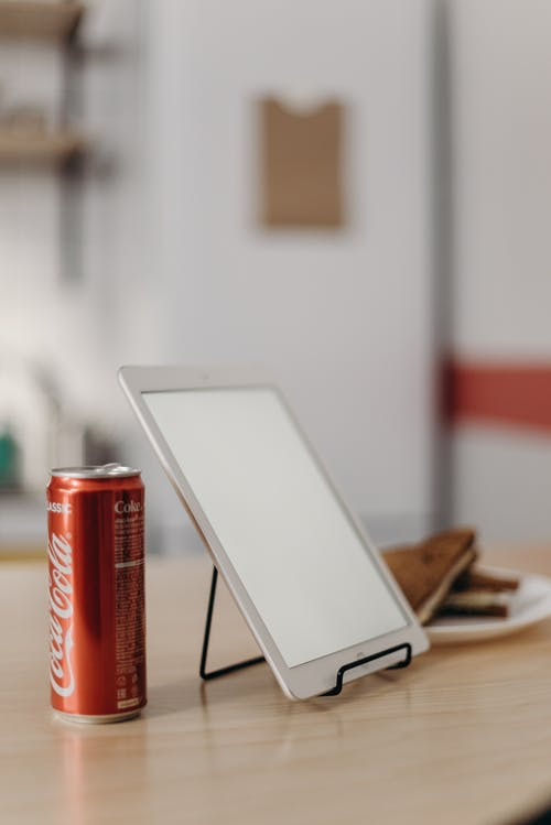 White Tablet Computer Beside Red Coca Cola Can