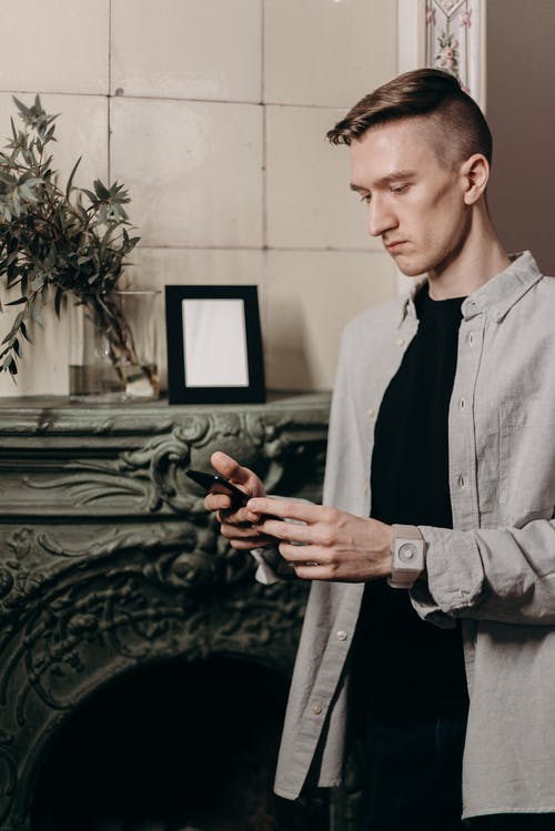 Man in Gray Dress Shirt Holding Black Smartphone