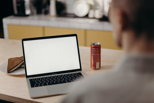 Red Can Beside Macbook Pro on Table