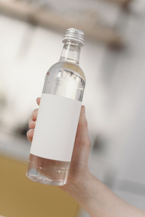 Photo Of Person Holding Clear Glass Bottle