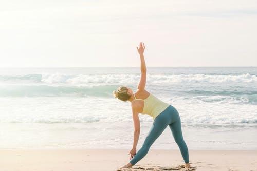 Woman in Yellow Tank Top and Blue Leggings Doing Yoga on Beach