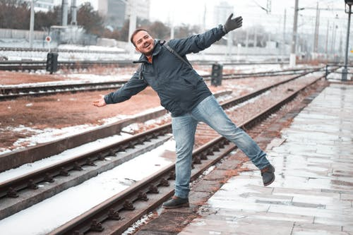Man in Black Jacket and Blue Denim Jeans Standing on Train Rail