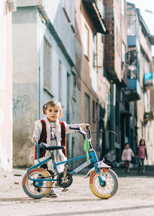 Girl Standing While Holding a Bicycle