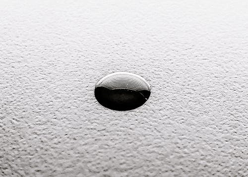 Small ink drop o white textured surface