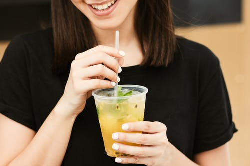 Woman in Black Shirt Holding Clear Plastic Cup With Straw