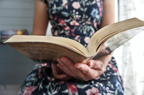 Person in Black and White Floral Dress Reading Book