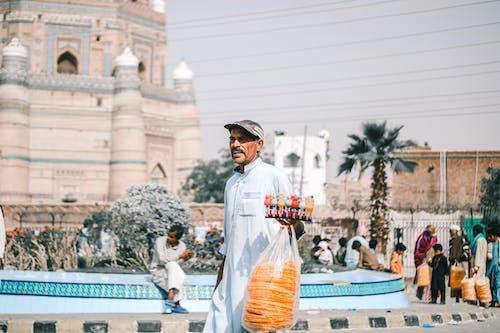 Man in White Crew Neck T-shirt and Black Cap Holding Orange Plastic Bag