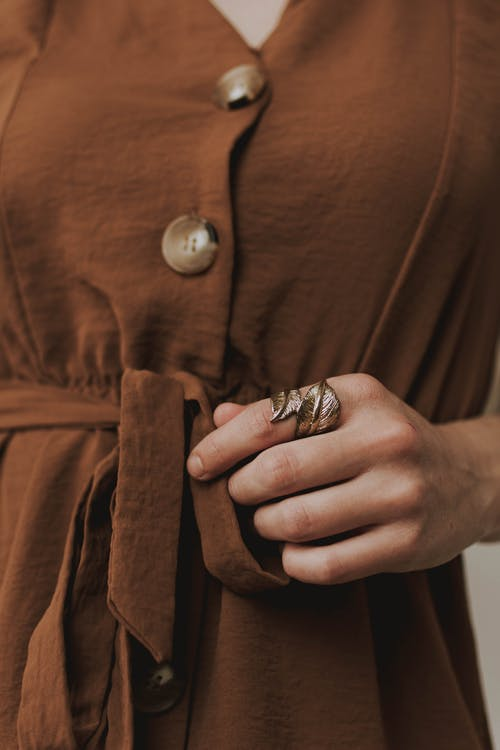 Person Wearing Silver Ring and Brown Button Up Shirt
