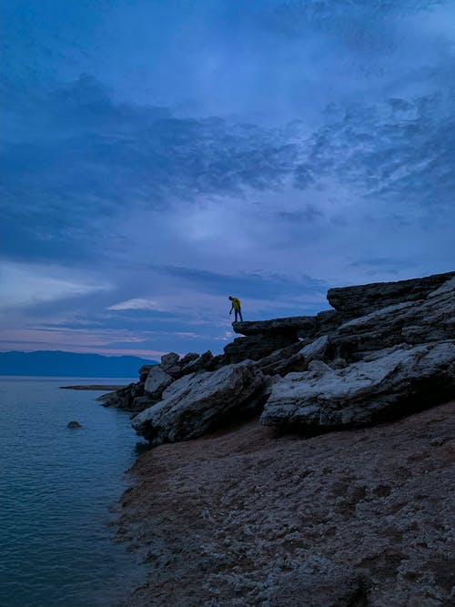 Person Standing on Rock Formation Near Body of Water
