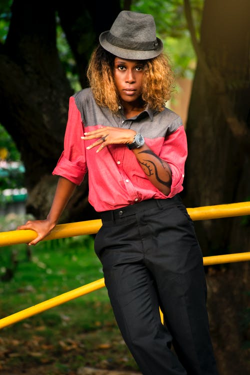 Woman in Pink Button Up Shirt and Black Pants Standing on Yellow Metal Railings