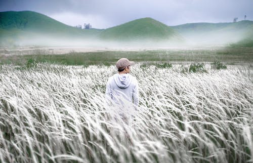 Man in White Hoodie Standing on Green Grass Field