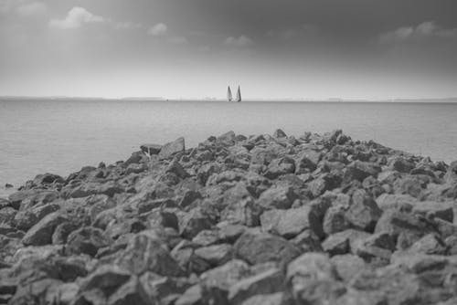 Grayscale Photo of Rocks Near Beach