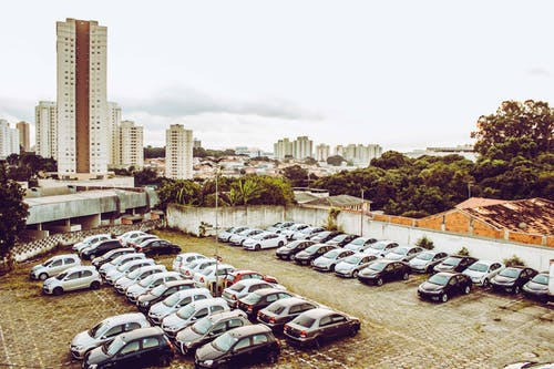 Cars Parked on Parking Lot Near High Rise Buildings