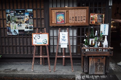 Wooden menu boards and various drinks on sidewalk near entrance of traditional oriental cafe during daytime