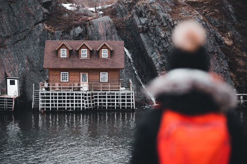 Person in Red Hoodie Standing Near Brown House Near Waterfalls