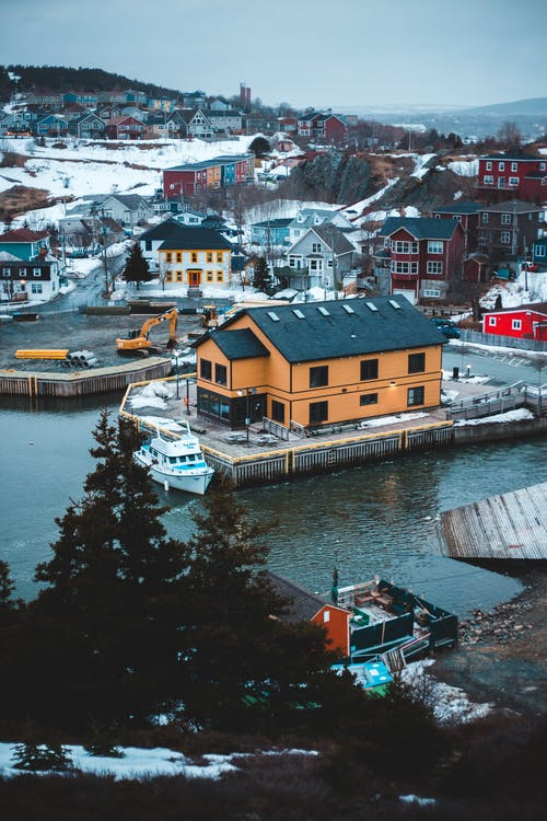 Picturesque village with colorful houses and calm lake on winter day