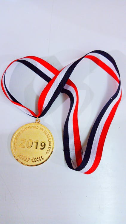 Gold Round Medal on White Surface