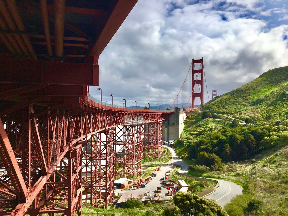 Red Bridge over River Under Cloudy Sky
