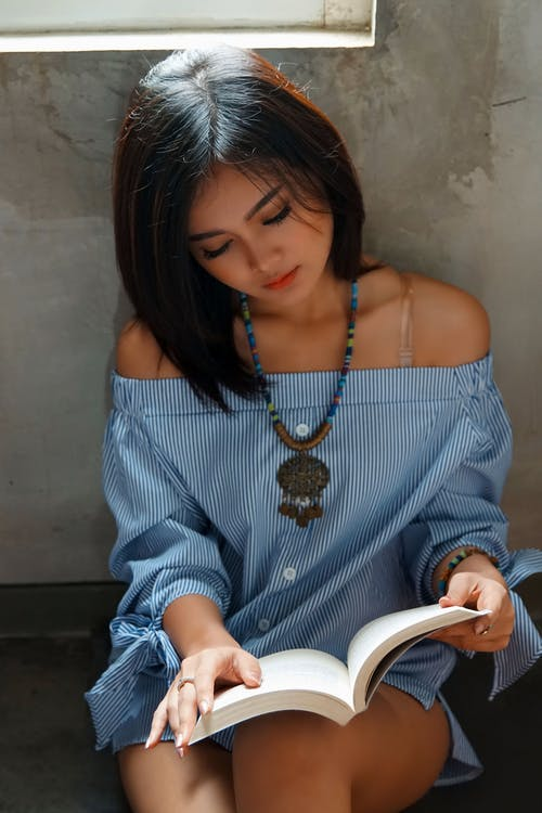 Woman in Blue and White Stripes Off Shoulder Dress Sitting On The Floor While Reading A Book