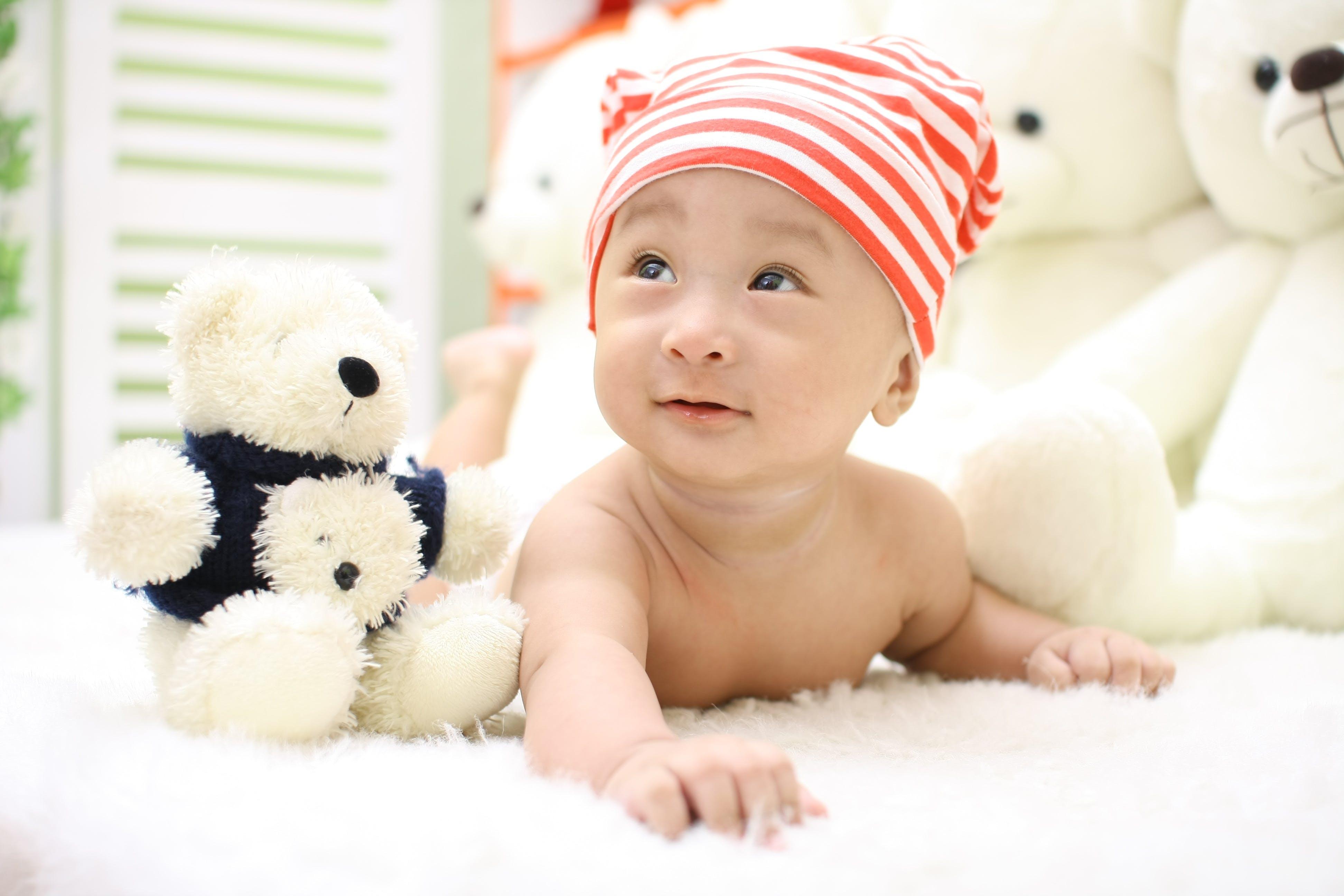 Smiling Toddler Wearing Orange and White Knit Cap Beside Black and White Bear Plush Toy